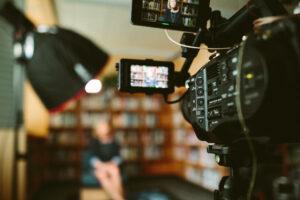 Donna seduta su poltrona ripresa da una videocamera in una stanza con libreria